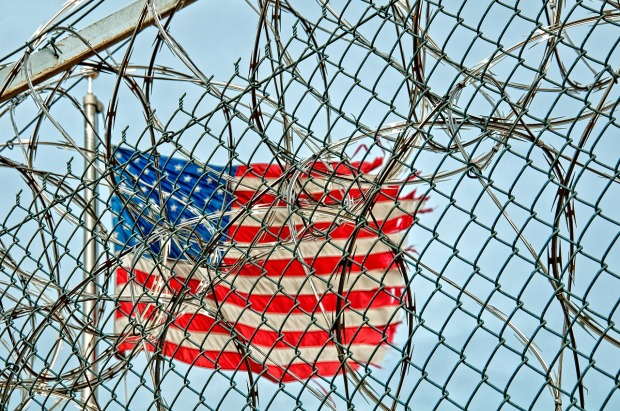 View of American Flag through barbed wire