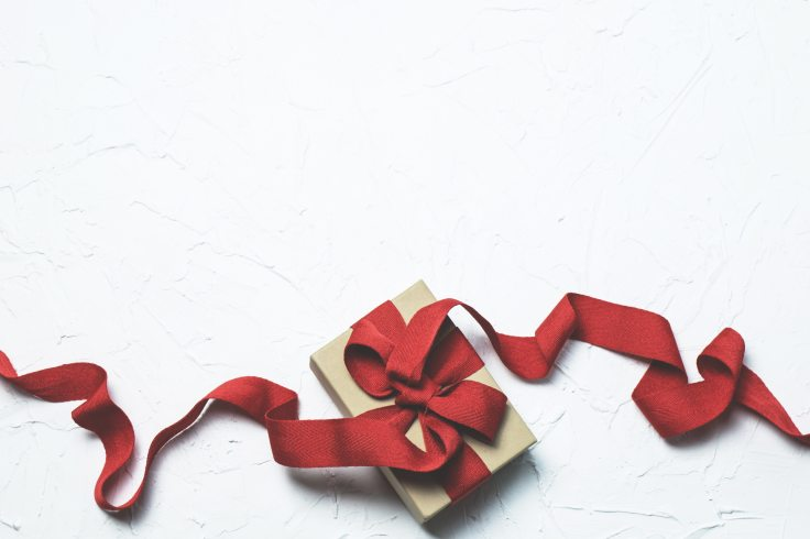 Wrapped book with long trailing red ribbon